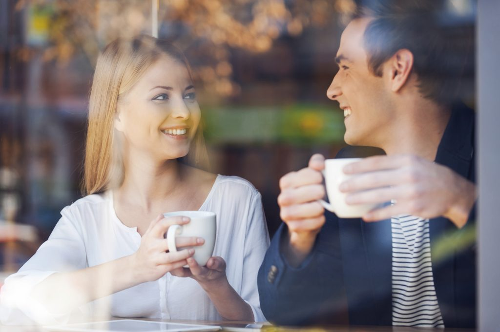 Enjoying fresh coffee together. Through a glass shot of beautiful young couple looking at each other and smiling while enjoying coffee in cafe together