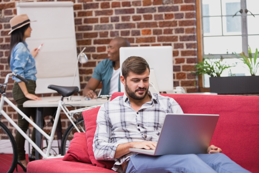 Man using laptop on couch in office iStock_000051563984_Small