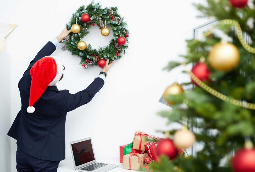 Man putting up office Christmas decorations.